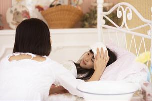子供のおでこにタオルをあてる母の写真素材 [FYI01767886]