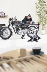 室内でバイクを眺める男性の写真素材 [FYI01768213]