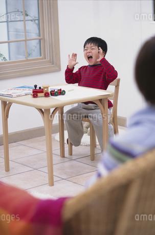 椅子の上で手を上げて笑う男の子の写真素材 [FYI01768238]
