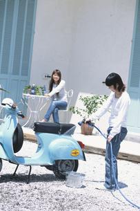 庭で水色のベスパを洗う女性2人の写真素材 [FYI01768368]