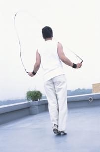 屋上で縄跳びをする男性の写真素材 [FYI01768399]