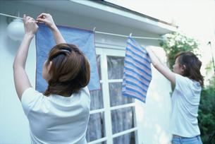 洗濯物をロープに干す2人の女性の写真素材 [FYI01768402]