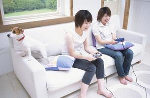 テレビゲームで遊ぶ女性2人と犬の写真素材 [FYI01768459]
