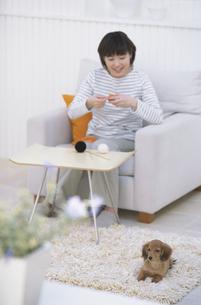 編み物をする女性と犬の写真素材 [FYI01768511]