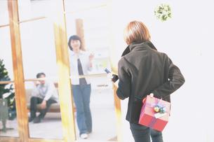 ワインとプレゼントを持って訪れる女性の写真素材 [FYI01768521]