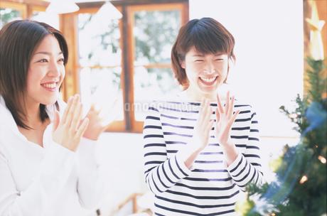 クリスマスツリーと拍手する2人の女性の写真素材 [FYI01768531]