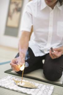 線香に火をつける男性の写真素材 [FYI01768548]