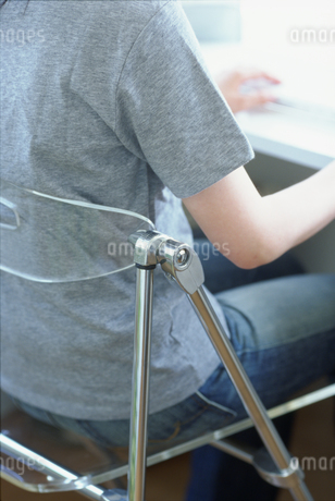 椅子に座りパソコンを操作する女性の写真素材 [FYI01768612]