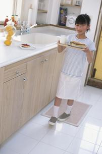 キッチンで食事を運ぶ女の子の写真素材 [FYI01768673]
