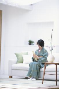 ソファに座る着物の女性の写真素材 [FYI01768681]