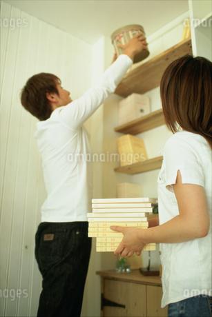 本棚を整理するカップルの写真素材 [FYI01768690]