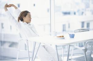 テーブルで伸びをする女性の写真素材 [FYI01768705]