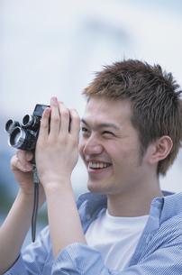 カメラを覗く男性の写真素材 [FYI01768939]