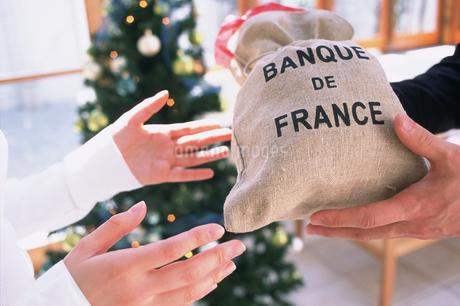 ツリーの前でプレゼントを渡す手の写真素材 [FYI01769316]