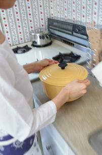 キッチンで黄色い鍋を持つ女性の写真素材 [FYI01769547]