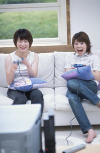 テレビゲームで遊ぶ女性2人の写真素材 [FYI01769586]