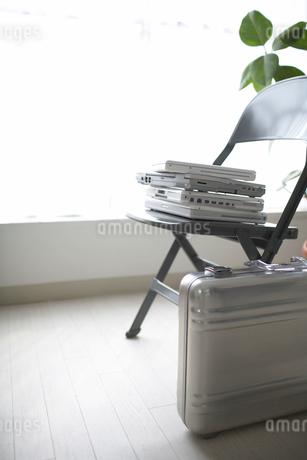 椅子の上のノートパソコンとジェラルミンケースの写真素材 [FYI01769699]