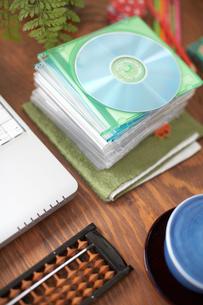 机の上の重ねたディスクやそろばんやノートPCの写真素材 [FYI01769870]