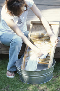 洗濯板で洗濯する女性の写真素材 [FYI01770053]