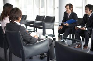 商談をしているビジネスマン3人とOLの写真素材 [FYI01770129]