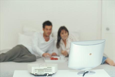 ベッドの上でテレビを見ているカップルの写真素材 [FYI01770245]