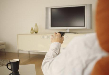 テレビの前でリモコンを持つ男性の手の写真素材 [FYI01770485]