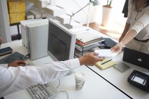 オフィスで小物の受け渡しをする手元の写真素材 [FYI01770602]