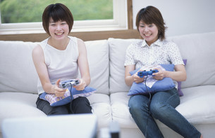 テレビゲームで遊ぶ女性2人の写真素材 [FYI01770622]