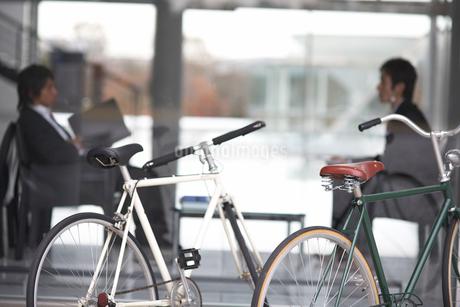 窓越しで会話しているビジネスマン2人の写真素材 [FYI01770647]