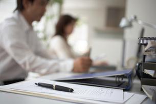 デスク上のファイルやペンと働く男女の写真素材 [FYI01770825]