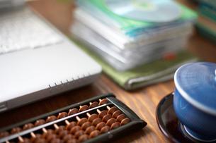 机の上の重ねたディスクやそろばんやノートPCの写真素材 [FYI01771672]
