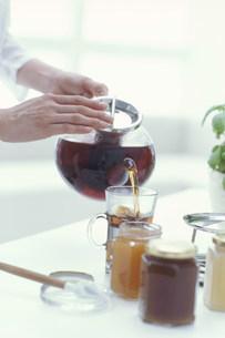 瓶詰のジャムと紅茶を入れる手元の写真素材 [FYI01771839]