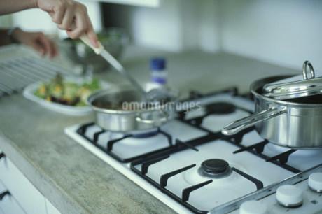 ガスコンロと料理をする手元の写真素材 [FYI01771922]