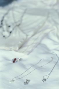 ベットに置いたペンダントとイヤリングの写真素材 [FYI01772082]