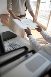 オフィスで書類の受け渡しをする手元の写真素材 [FYI01772324]