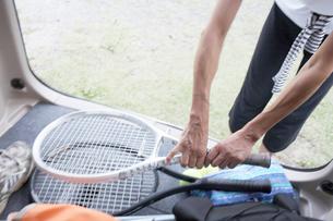 車に積んだテニスラケットを取る女性の写真素材 [FYI01773168]