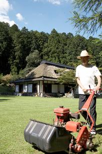 芝を刈る男性 日本家屋の写真素材 [FYI01773180]
