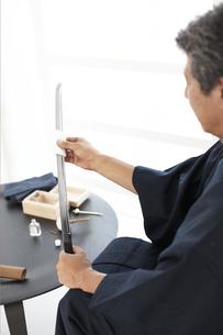 日本刀の手入れをする着物の男性の写真素材 [FYI01773187]