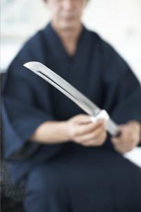 日本刀の手入れをする着物の男性の写真素材 [FYI01773203]