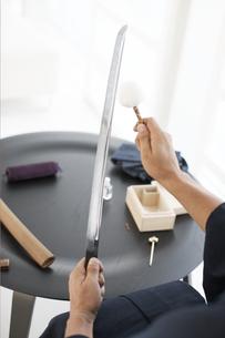 日本刀の手入れをする着物の男性の写真素材 [FYI01773429]
