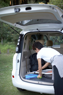 車に積んだテニスラケットを取る女性の写真素材 [FYI01773709]