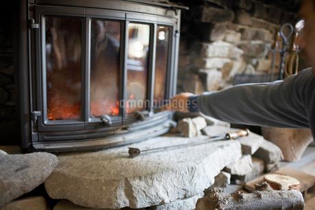 暖炉の扉を閉める男性の写真素材 [FYI01774189]