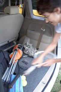 車に積んだテニスラケットを取る女性の写真素材 [FYI01774397]