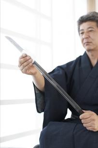 日本刀の手入れをする着物の男性の写真素材 [FYI01774663]