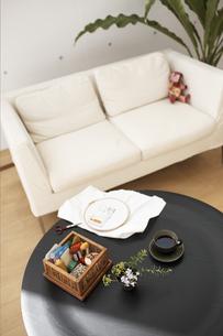 テーブルの上の刺繍セットとコーヒーとソファの写真素材 [FYI01775075]
