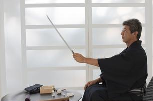 日本刀の手入れをする着物の男性の写真素材 [FYI01775190]