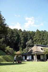 芝を刈る男性 日本家屋の写真素材 [FYI01775257]