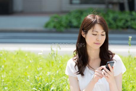 屋外で携帯電話を使う美しい女性の写真素材 [FYI01775975]