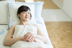 ベッドに寝転ぶ女性の写真素材 [FYI01776078]