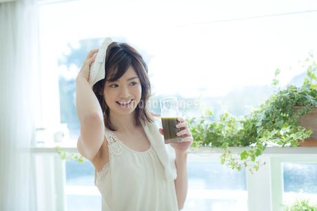 シャワー後に野菜ジュースを飲む女性の写真素材 [FYI01776086]